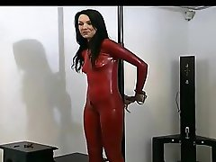 Tied up dark-haired angel in red latex and high heels enjoys posing in front of the cam