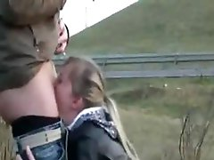 Blonde is on her knees engulfing his penis on the side of the road