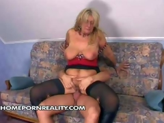 Heavy chested blonde momma with tanned body and huge tits enjoys in giving head on her knees and riding a hard bazooka on the couch in front of the cam