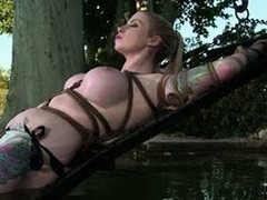 Inked up blonde chick gets tied up and dipped on every side along to cool water