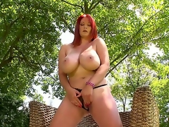 Fascinating redhead woman with perfect parts of body stays in high heels merely before starting to play with luscious pussy very well right in a garden. Watch her playing with twat!
