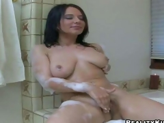 Naked brunette with big natural boobies takes a bubble bath before she parts her legs to stroke her meaty moist pussy with her fingers. She displays her sexy juggs as she masturbates