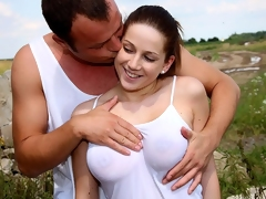 A young couple is playing hide and try to find on de side of a hill. After a while the guy stands behind the girl and plays with her tits. When they are both naked he licks her pussy. Then he fucks her from behind and comes over her tits.