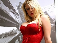 A blonde girl with bg tits and dressed in a tight corset is standing...
